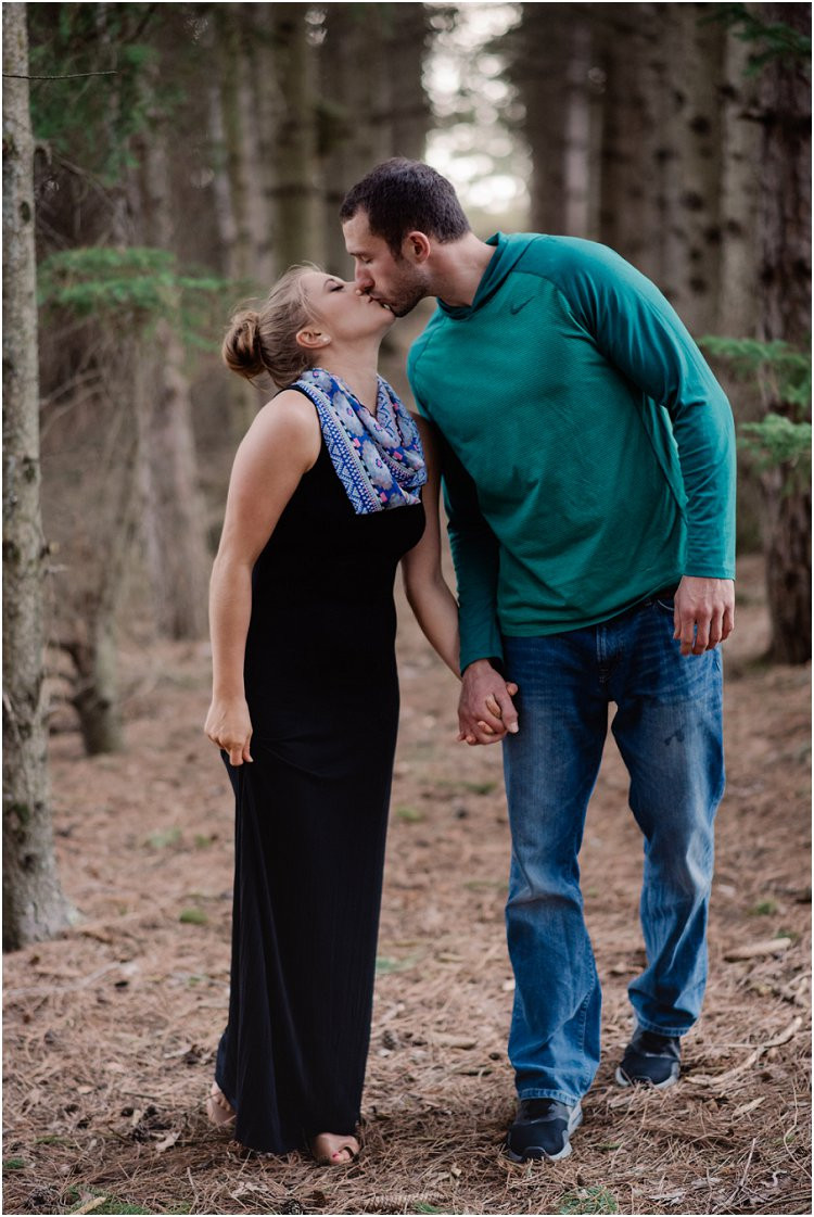 engaged-couple-holding-hands-and-kissing-under-pine-trees-at-hortonville-engagement-session-by-appleton-wedding-photographer-kyra-rane-photography