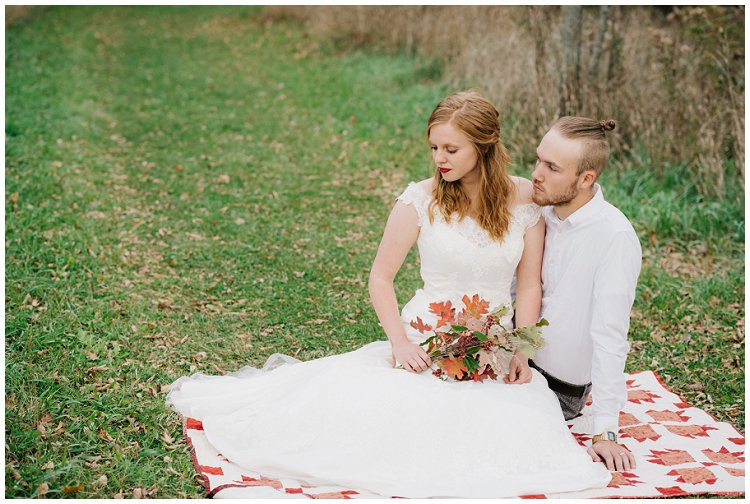 husband-and-wife-sitting-on-blanket-in-woods-at-anniversary-session-at-high-cliff-state-park-by-green-bay-wedding-photographer-kyra-rane-photography