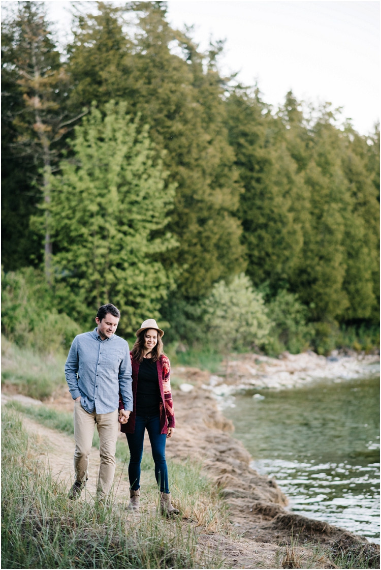 engaged-couple-smiling-by-lake-at-cave-point-engagement-session-by-appleton-wedding-photographer-kyra-rane-photography