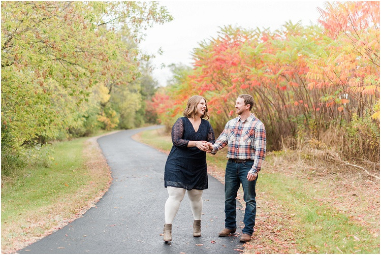 engaged-couple-laughin-on-road-at-high-cliff-engagement-session-by-green-bay-wedding-photographer-kyra-rane-photography