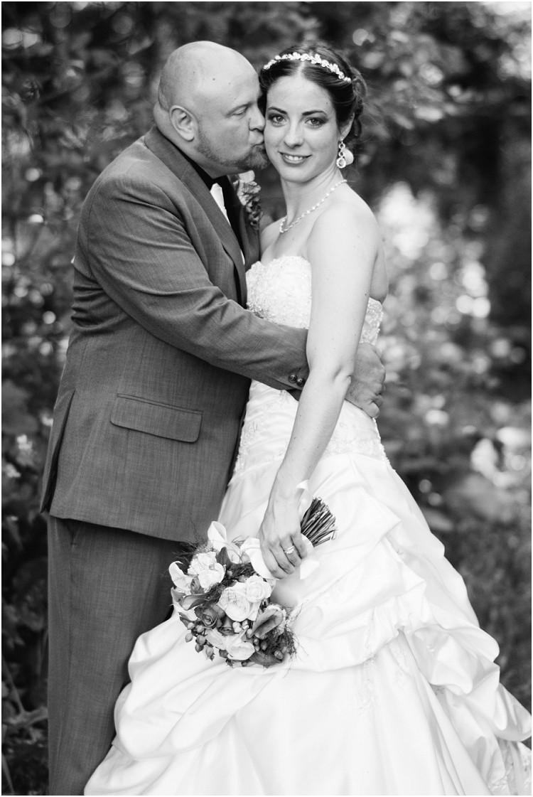 groom-kissing-bride-on-cheek-at-wisconsin-farm-wedding-by-green-bay-wedding-photographer-kyra-rane-photography