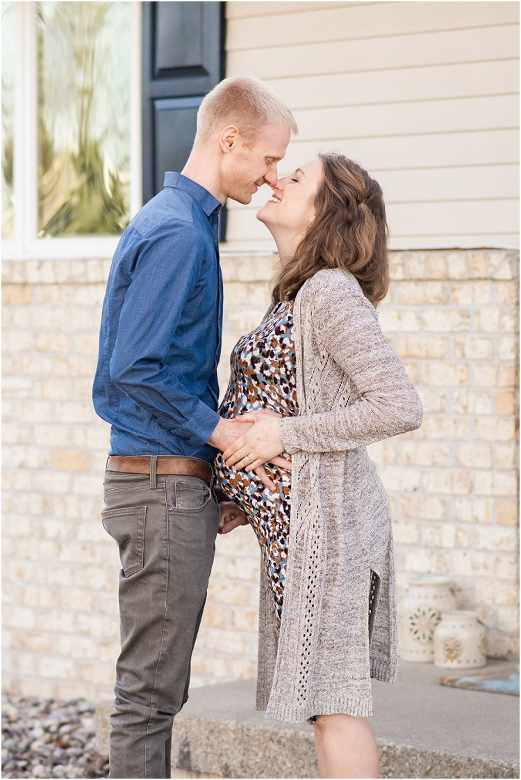 mother-and-father-to-be-with-hands-on-bump-about-to-kiss-at-the-front-porch-series-by-green-bay-wedding-photographer-kyra-rane-photography
