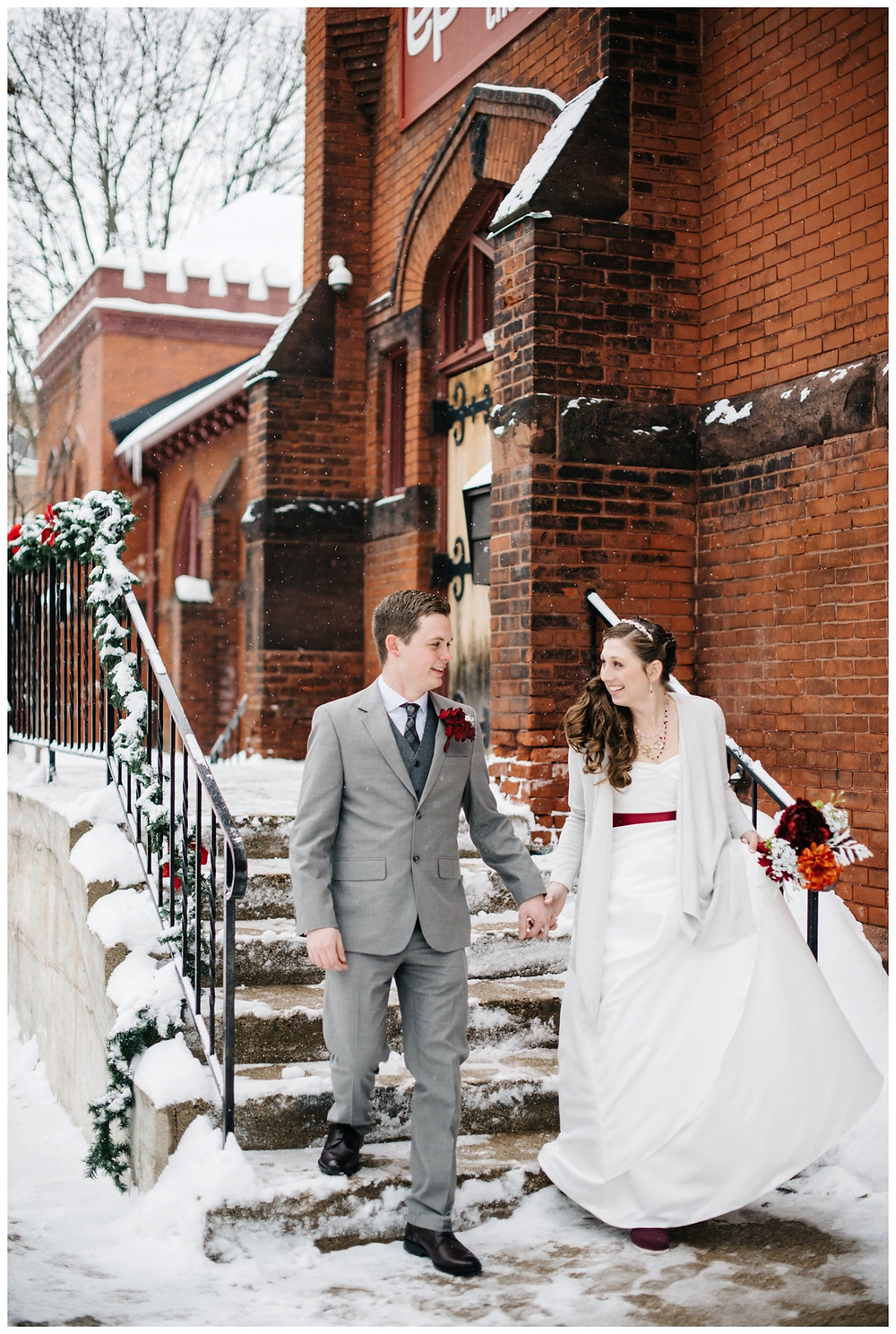 bride-and-groom-smiling-down-snowy-steps-at-milwaukee-wedding-by-milwaukee-wedding-photographer-kyra-rane-photographer