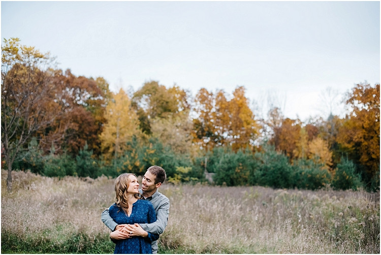 couple-cuddling-with-autumn-treeline-at-fall-mini-session-favorites-by-green-bay-wedding-photographer-kyra-rane-photography