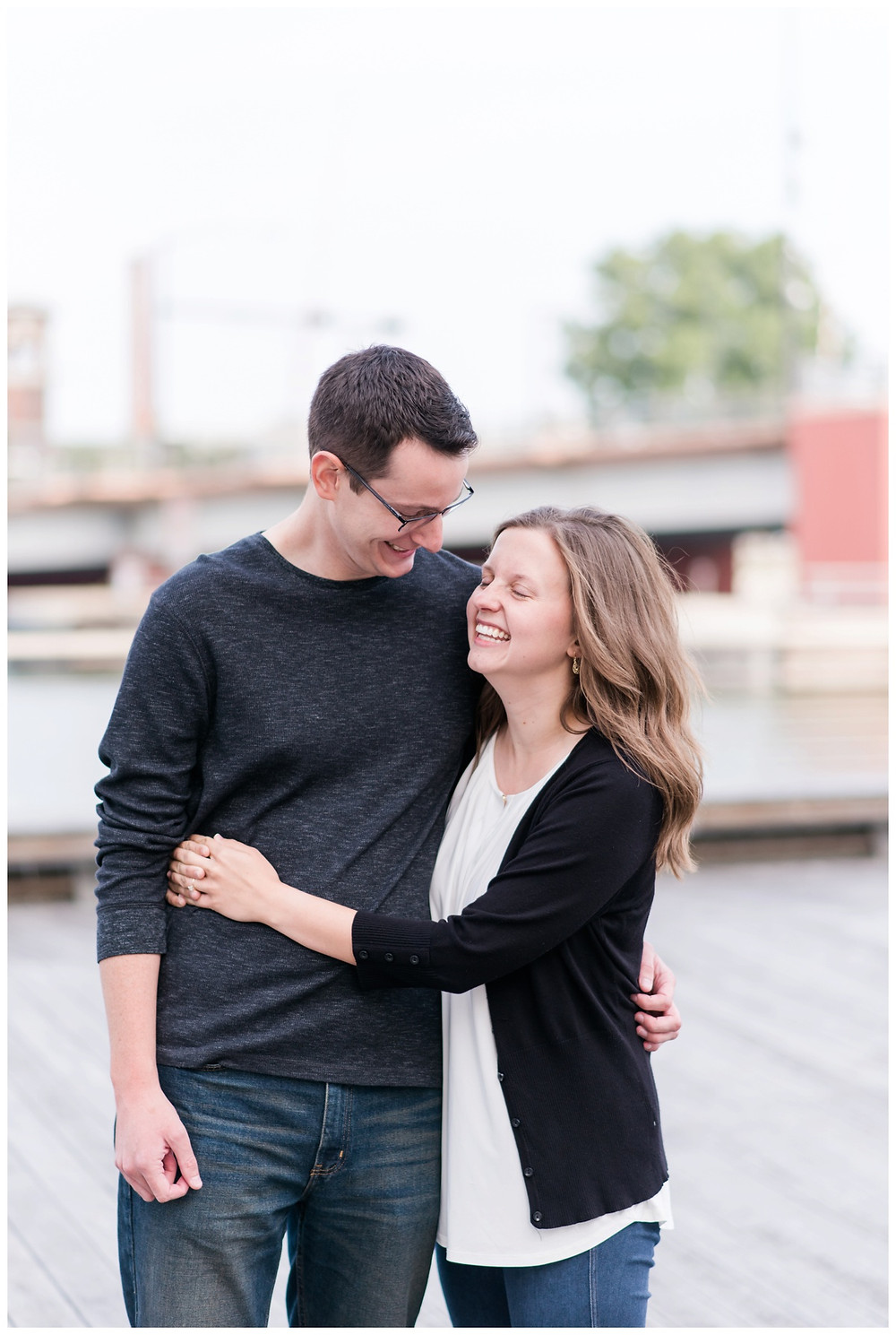 engaged-couple-arms-around-each-other-laughing-at-downtown-green-bay-engagement-session-by-appleton-wedding-photographer-kyra-rane-photography