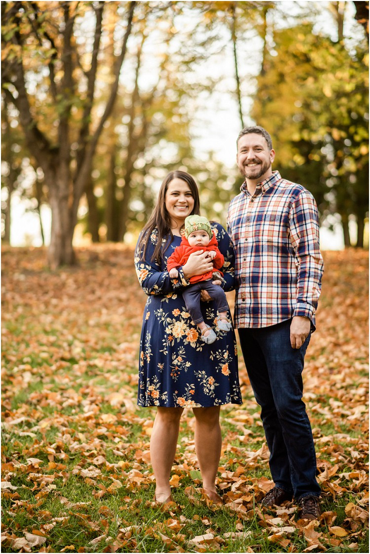 family-smiling-at-camera-with-baby-on-fall-day-at-plamann-park-by-green-bay-wedding-photographer-kyra-rane-photgraphy