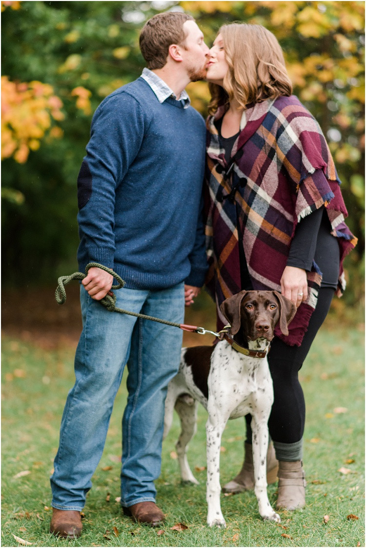 engaged-couple-kiss-on-trail-with-dog-at-high-cliff-engagement-session-by-green-bay-wedding-photographer-kyra-rane-photography