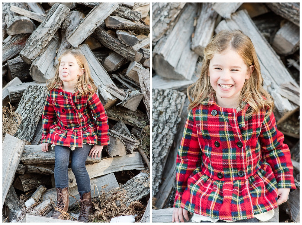 little-girl-laughing-in-front-of-logs-at-northwoods-lifestyle-session-by-green-bay-wedding-photographer-kyra-rane-photography