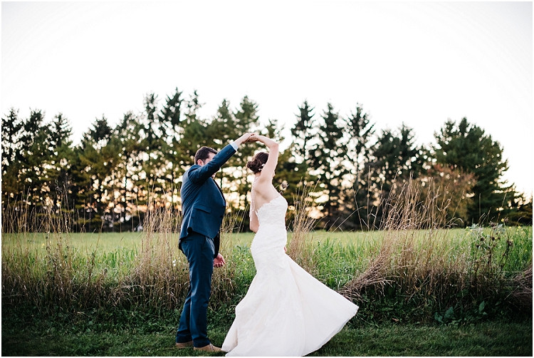groom-twirling-bride-at-sunset-at-barnsite-retreat-and-events-wedding-by-milwaukee-wedding-photographer-kyra-rane-photography
