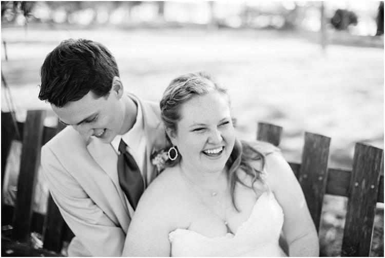 bride-and-groom-sitting-on-bench-laughing-at-minnesota-wedding-by-milwaukee-wedding-photographer-kyra-rane-photography