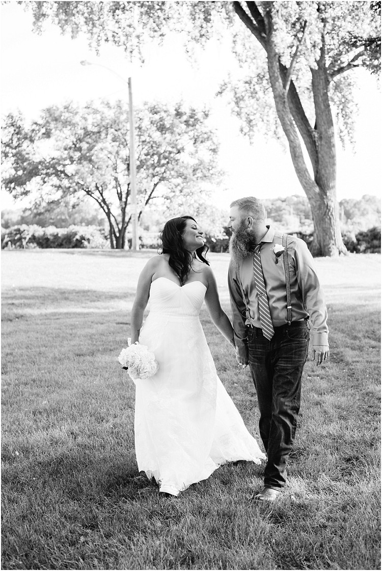 wedding-couple-holding-hands-walking-and-smiling-at-little-chute-waterfront-wedding-by-appleton-wedding-photographer-kyra-rane-photography