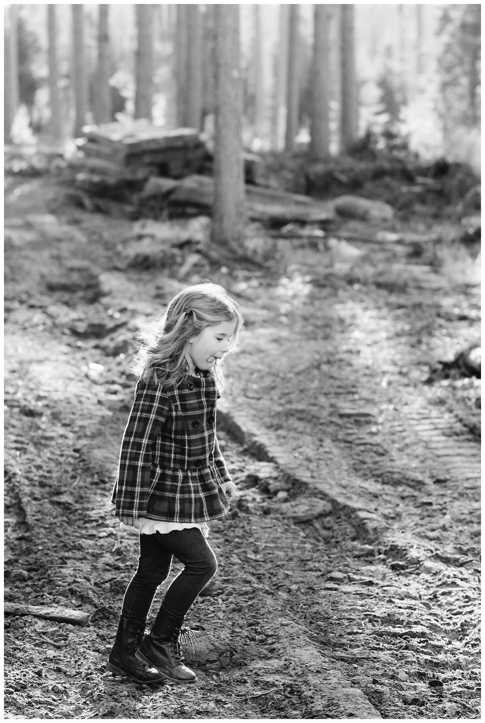 little-girl-walking-with-tounge-sticking-out-at-northwoods-lifestyle-session-by-green-bay-wedding-photographer-kyra-rane-photography