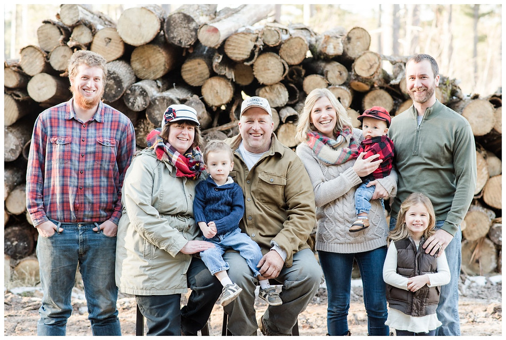 family-picture-in-front-of-logs-smiling-at-northwoods-lifestyle-session-by-milwaukee-wedding-photographer-kyra-rane-photography