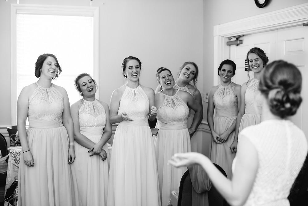 bridesmaids-smiling-at-bride-in-wedding-dress-at-how-to-be-a-dream-bridesmaid-by-green-bay-wedding-photographer-kyra-rane-photography