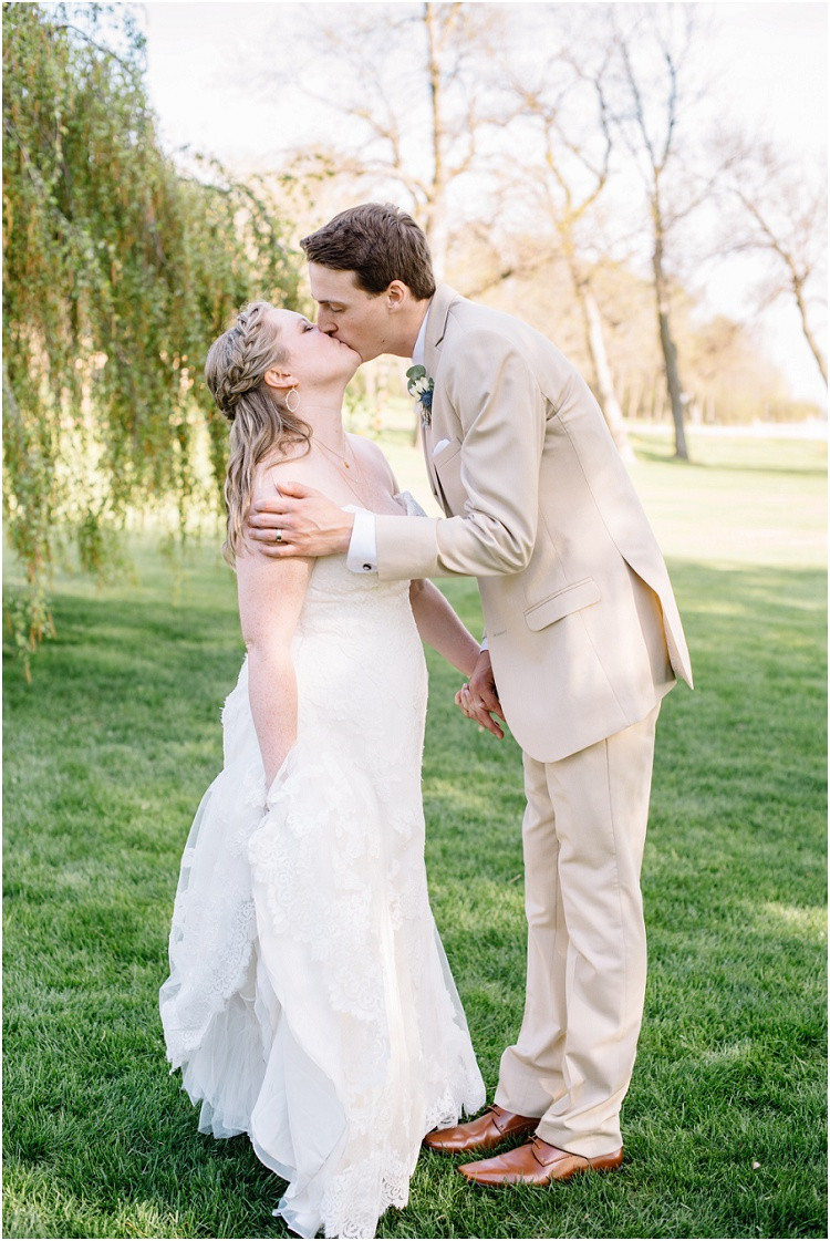 bride-and-groom-holding-hands-and-kissing-at-minnesota-wedding-by-green-bay-wedding-photographer-kyra-rane-photography