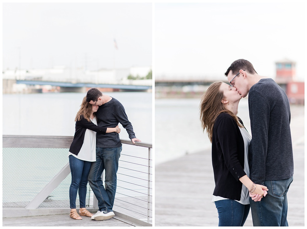 engaged-couple-leaning-against-railing-hugging-at-downtown-green-bay-engagement-session-by-appleton-wedding-photographer-kyra-rane-photography
