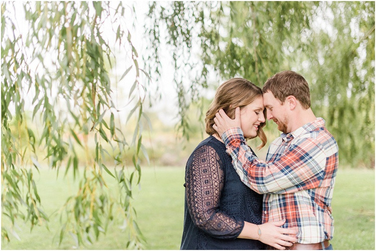 engaged-couple-foreheads-together-under-willow-tree-at-high-cliff-engagement-session-by-milwaukee-wedding-photographer-kyra-rane-photography