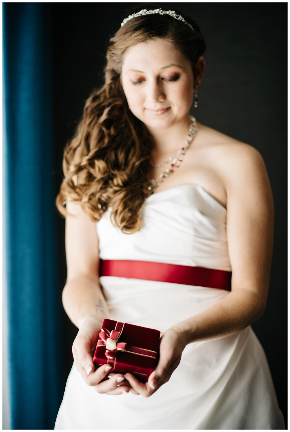 bride-holding-red-ribboned-gift-at-milwaukee-wedding-by-green-bay-wedding-photographer-kyra-rane-photographer