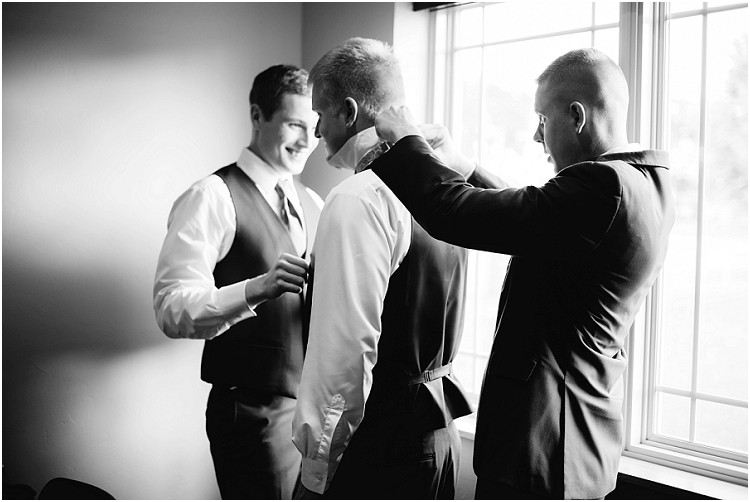 groom-putting-on-tie-at-de-pere-wedding-by-appleton-wedding-photographer-kyra-rane-photography