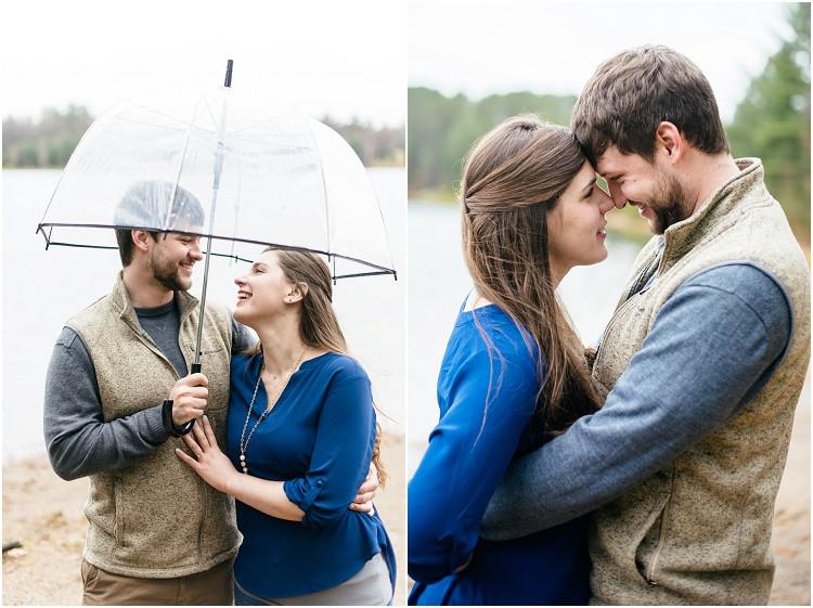 engaged-couple-laughing-under-umbrella-at-northwoods-lakeside-engagement-session-by-green-bay-wedding-photographer-kyra-rane-photography