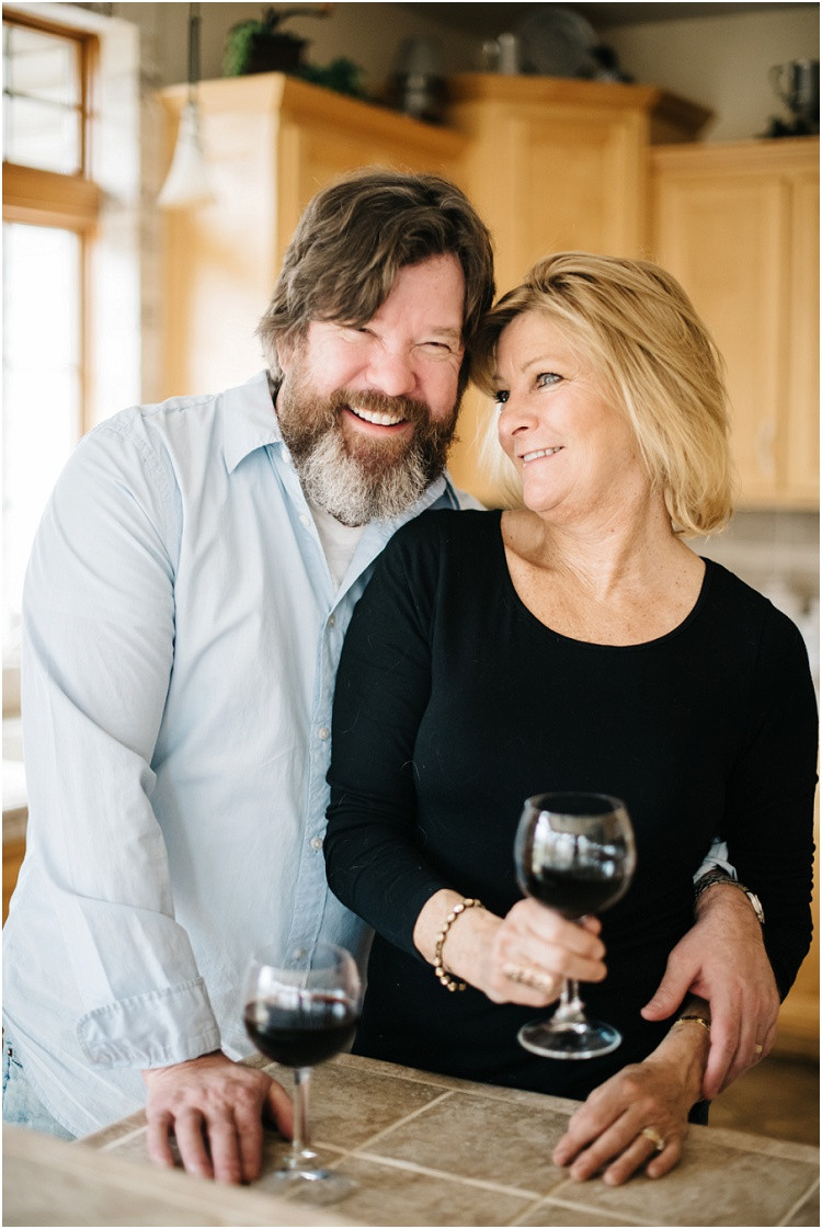 husband-and-wife-toasting-with-glasses-of-wine-in-kitchen-at-in-home-anniversary-session-by-appleton-wedding-photographer-kyra-rane-photography
