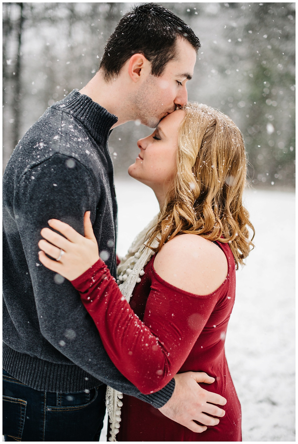 guy-kissing-womans-forehead-at-snowy-sheboygan-engagement-session-by-milwaukee-wedding-photographer-kyra-rane-photography