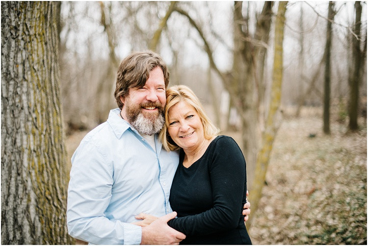 husband-and-wife-smiling-at-camera-in-each-others-arms-at-in-home-anniversary-session-by-appleton-wedding-photographer-kyra-rane-photography