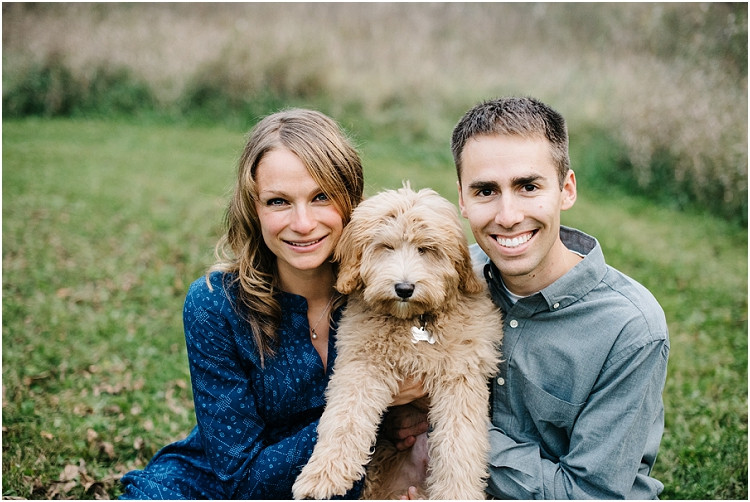 couple-smiling-at-camera-with-new-puppy-at-fall-mini-session-favorites-by-appleton-wedding-photographer-kyra-rane-photography