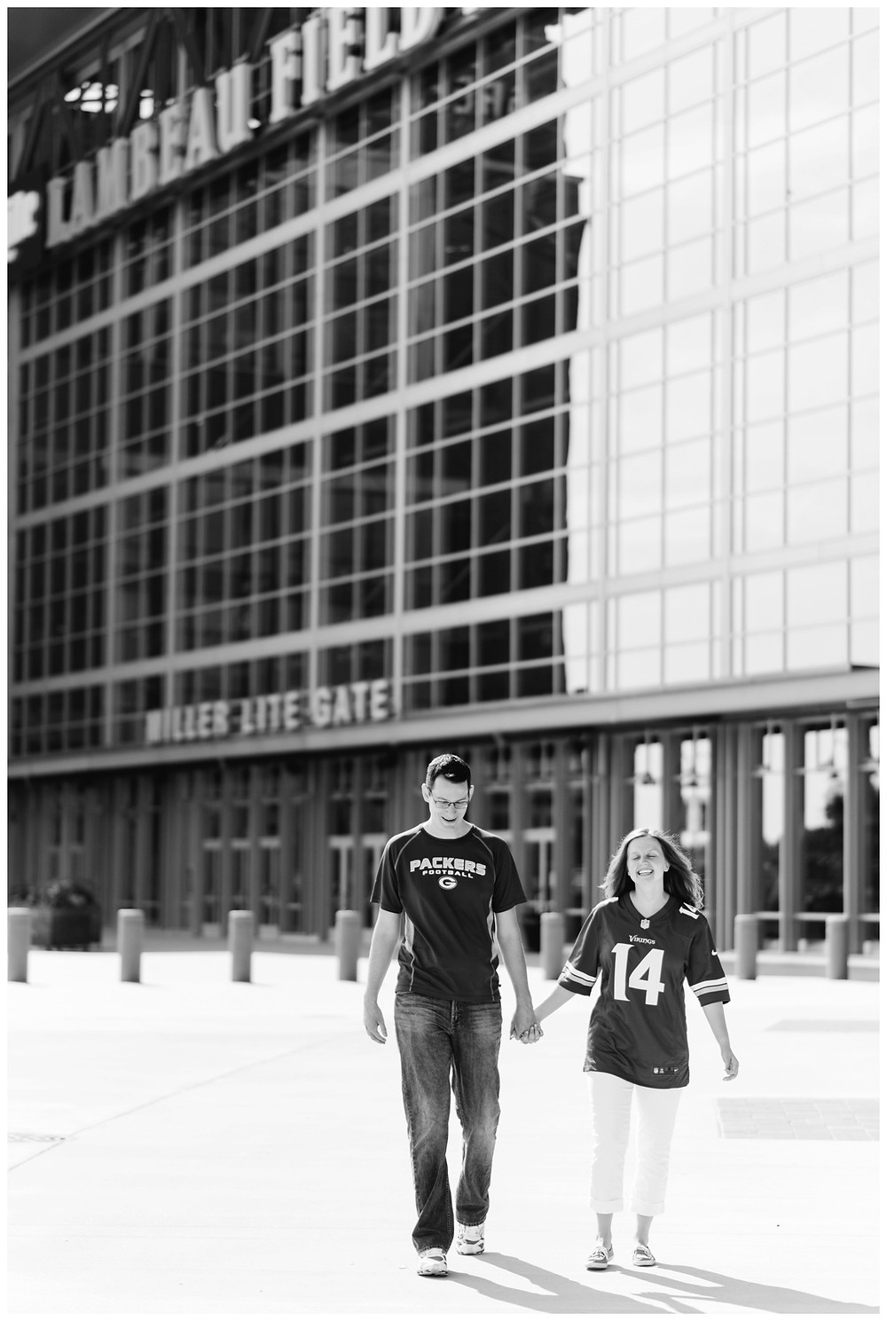 engaged-couple-walking-away-from-stadium-at-downtown-green-bay-engagement-session-by-green-bay-wedding-photographer-kyra-rane-photography