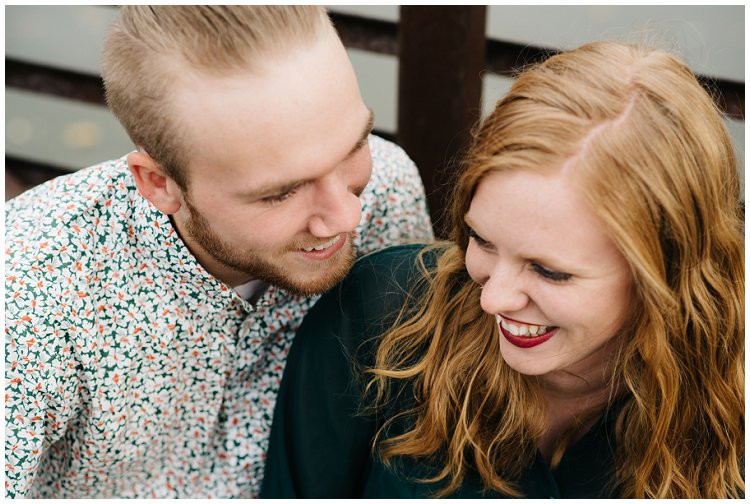 husband-and-wife-sitting-on-bridge-smiling-at-anniversary-session-at-high-cliff-state-park-by-appleton-wedding-photographer-kyra-rane-photography