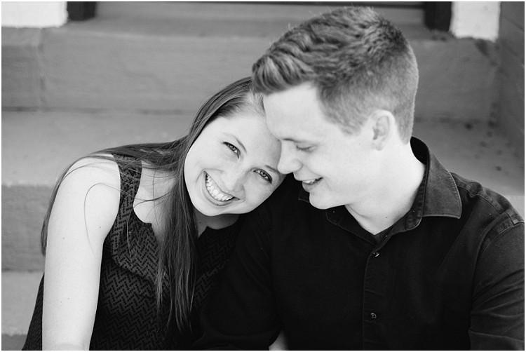 couple-sitting-on-steps-smiling-at-milwaukee-lighthouse-engagement-session-by-appleton-wedding-photographer-kyra-rane-photography