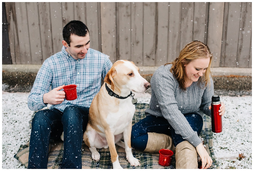 engaged-couple-with-pup-drinking-hot-chocolate-at-snowy-sheboygan-engagement-session-by-appleton-wedding-photographer-kyra-rane-photography