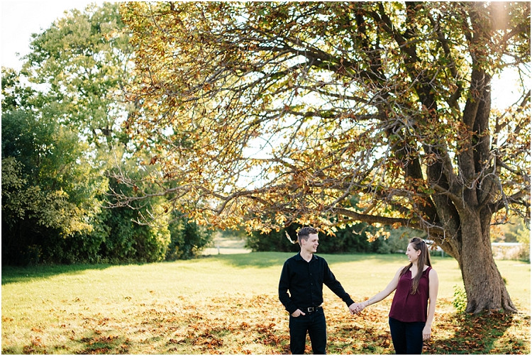 couple-holding-hands-under-tree-at-milwaukee-lighthouse-engagement-session-by-appleton-wedding-photographer-kyra-rane-photography