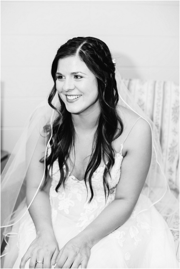 bride-sitting-and-smiling-in-white-lace-wedding-dress-at-de-pere-wisconsin-wedding-by-appleton-wedding-photographer-kyra-rane-photography