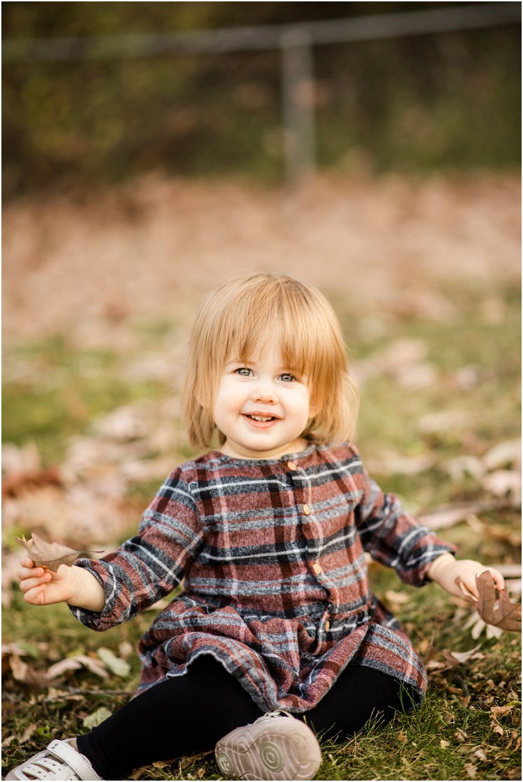 toddler-sitting-in-leaves-at-backyard-family-session-by-green-bay-wedding-photographer-kyra-rane-photography