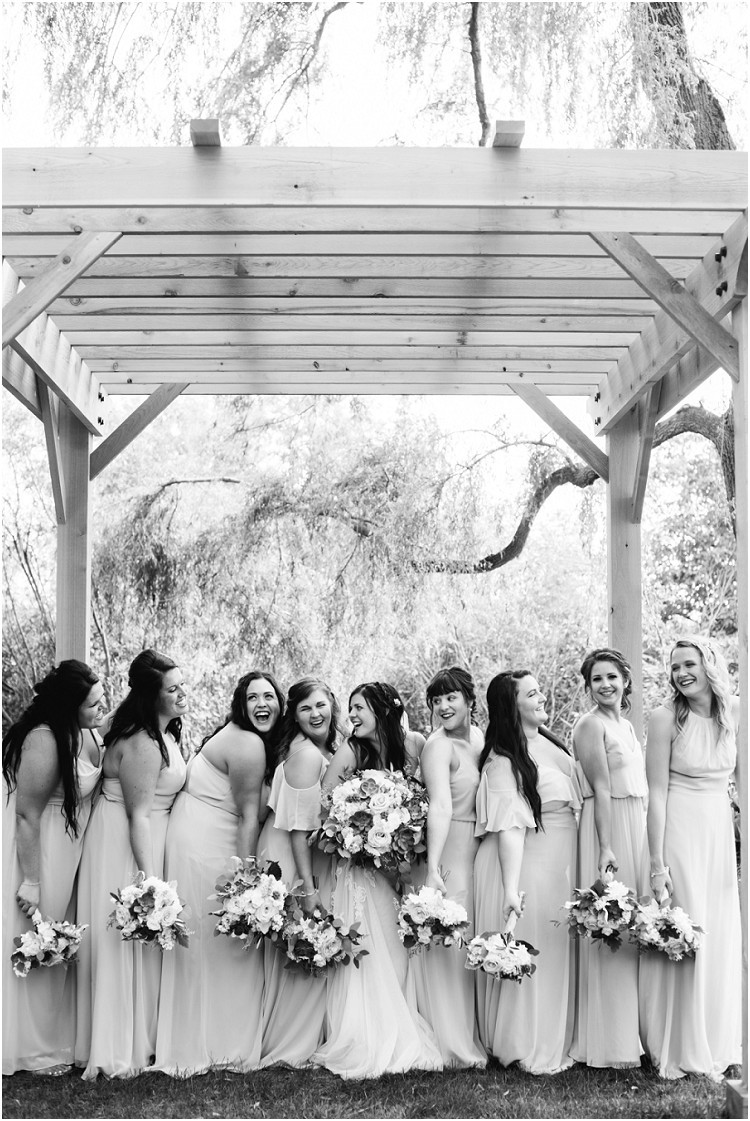 bridesmaids-laughing-under-arch-at-de-pere-wisconsin-wedding-by-appleton-wedding-photographer-kyra-rane-photography