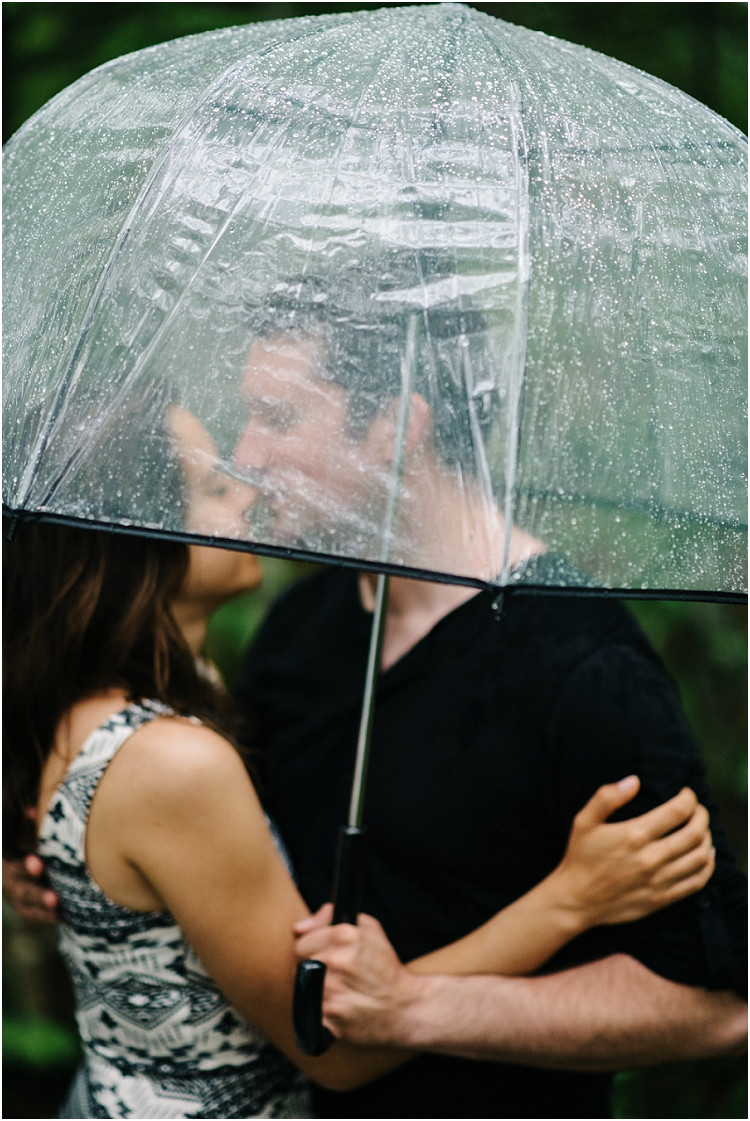 engaged-couple-under-umbrella-at-cave-point-engagement-session-by-appleton-wedding-photographer-kyra-rane-photography