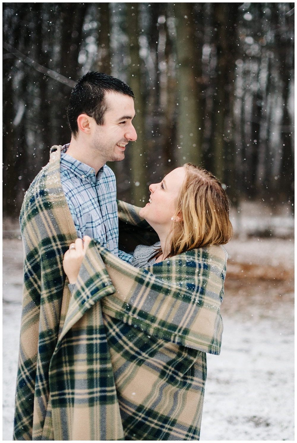 engaged-couple-laughing-under-blanket-at-snowy-sheboygan-engagement-session-by-green-bay-wedding-photographer-kyra-rane-photography