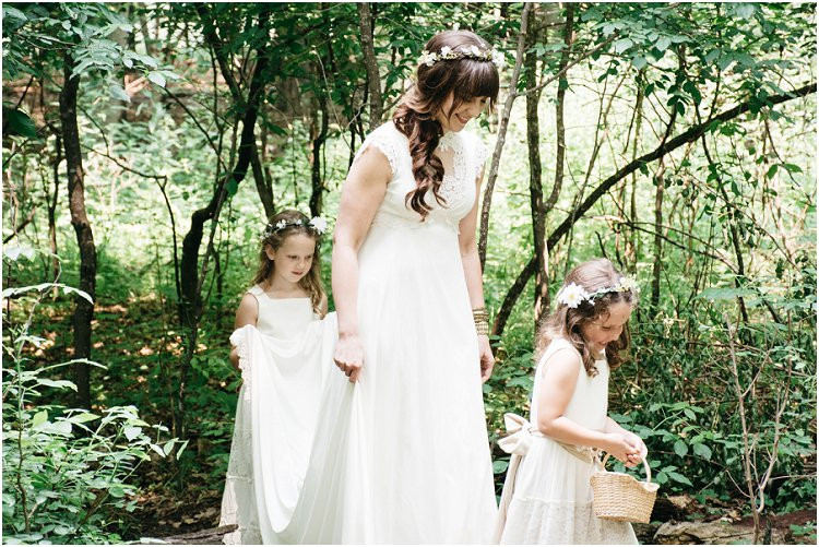 bride-walking-down-forest-aisle-with-flower-girls-at-july-4th-elopement-by-appleton-wedding-photographer-kyra-rane-photography