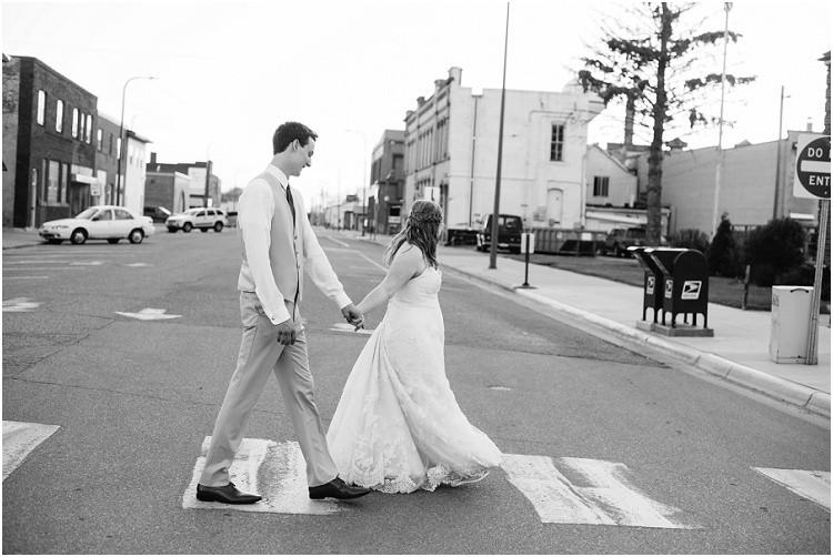 wedding-couple-cross-street-at-minnesota-wedding-by-green-bay-wedding-photographer-kyra-rane-photography