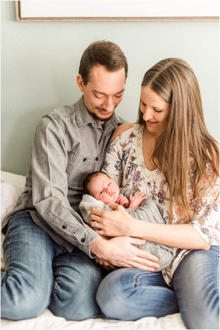 parents-holding-at-looking-at-newborn-baby-at-cozy-newborn-session-by-milwaukee-wedding-photographer-kyra-rane-photography