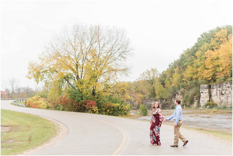 engaged-couple-cross-road-holding-hands-at-high-cliff-engagement-session-by-appleton-wedding-photographer-kyra-rane-photography
