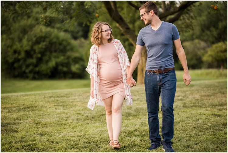expecting-couple-walking-and-holding-hands-smiling-at-plamann-park-maternity-session-by-green-bay-wedding-photographer-kyra-rane-photography