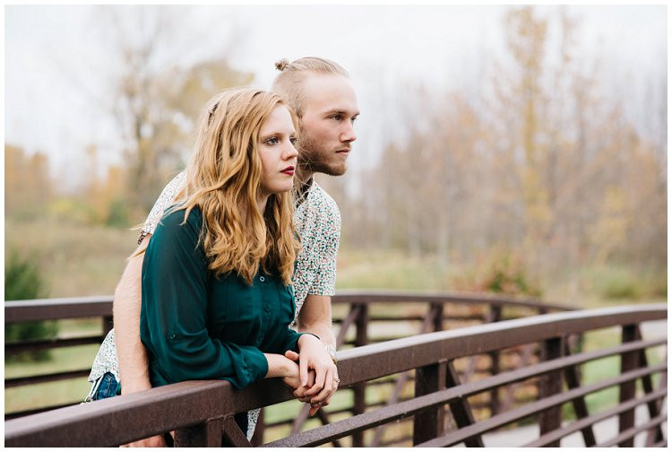 husband-and-wife-looking-out-from-bridge-at-anniversary-session-at-high-cliff-state-park-by-appleton-wedding-photographer-kyra-rane-photography