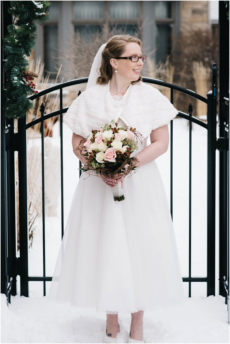 bride-standing-in-snow-with-bouquet-at-sheboygan-winter-wedding-by-appleton-wedding-photographer-kyra-rane-photography