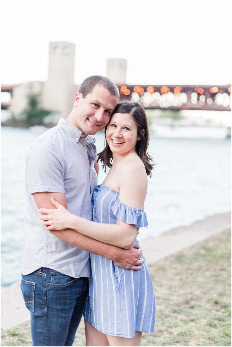 husband-and-wife-smiling-at-camera-by-river-at-downtown-chicago-anniversary-session-by-green-bay-wedding-photographer-kyra-rane-photography