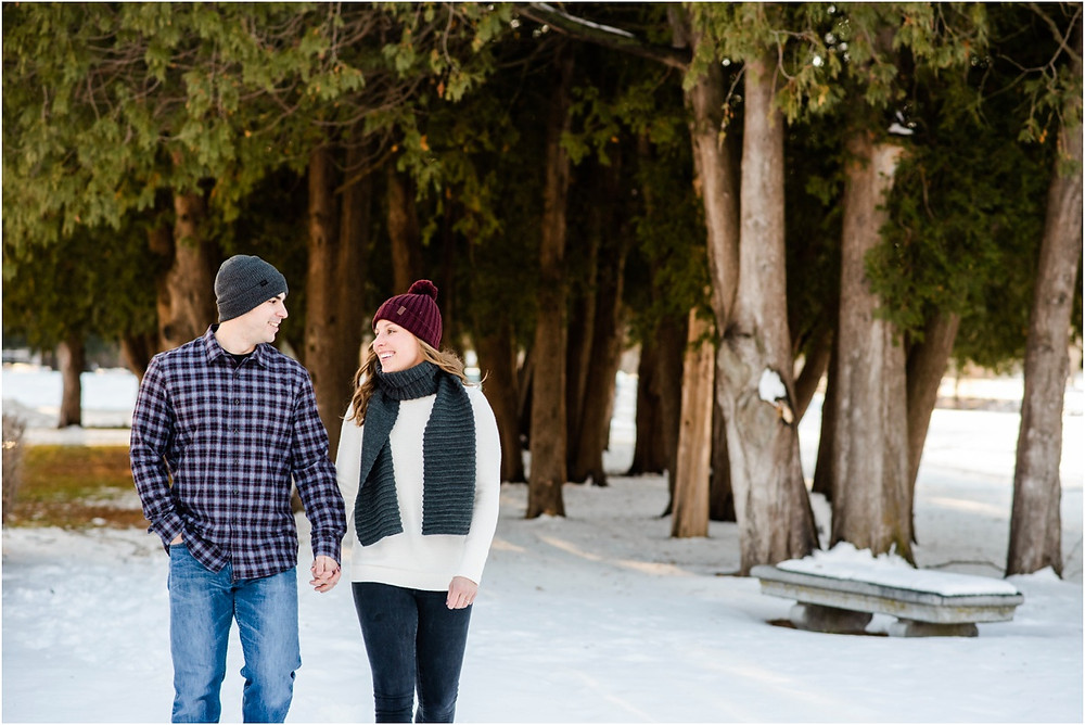 engaged-couple-walking-towards-camera-at-pamperin-park-winter-engagement-session-by-appleton-wedding-photographer-kyra-rane-photography