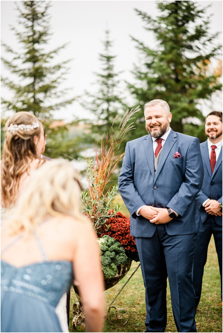 groom-smiling-at-bride-at-end-of-aisle-at-northern-wisconsin-autumn-wedding-by-appleton-wedding-photographer-kyra-rane-photography
