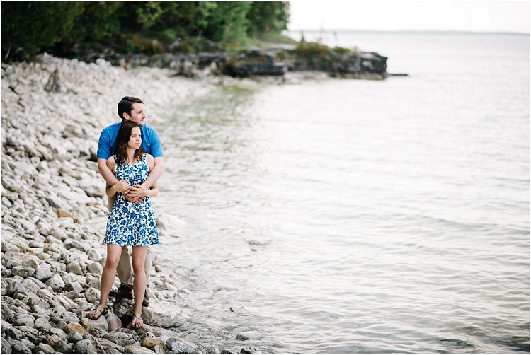 engaged-couple-looking-out-at-lake-at-cave-point-engagement-session-by-appleton-wedding-photographer-kyra-rane-photography