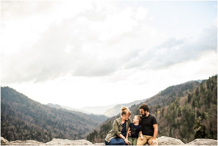 family-sitting-on-rock-ledge-with-mountain-view-at-family-session-in-the-great-smoky-mountains-by-appleton-wedding-photographer-kyra-rane-photography